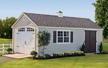 Vinyl A frame garage with cupola, wooden side door, double window with shutters, and wooden ramp