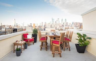 Keystone fire table and chairs on rooftop overlooking city.