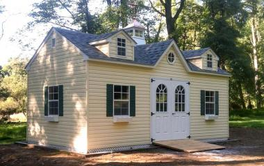 Vinyl a-frame storage shed with cupola, three dormers, double door, three windows, and wooden ramp