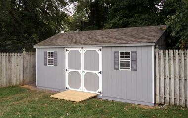 Wooden a-frame storage shed with double doors, two windows, and wooden ramp