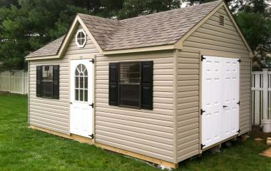Vinyl a-frame storage shed with two windows, gable vents, double steel doors, single 10-lite door, and dormer