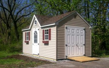Vinyl A-Frame style Storage Shed with dormer, double doors, two windows, single side door, and wooden ramp