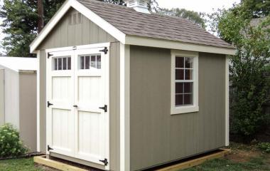 Wooden cape cod storage shed with cupola, double doors, and two windows