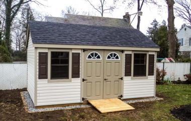 Vinyl cape cod storage shed with two windows, double doors, and wooden ramp