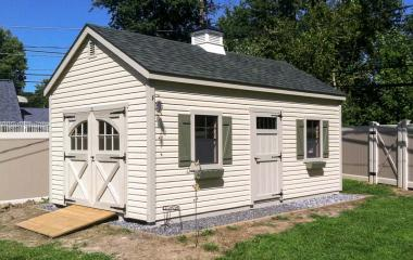 Vinyl cape cod storage shed with double doors, cupola, and wooden ramp