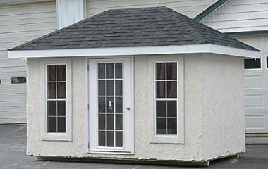 Hip roof storage shed with 15-lite door and two 8-lite windows