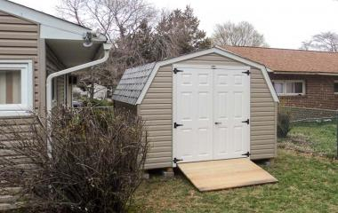 Vinyl Mini barn with double steel slab doors and wooden ramp