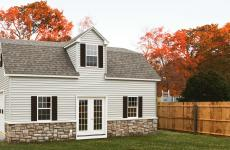 Vinyl Two story shed with garage door, stone skirting and dormer