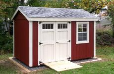 Wooden A-Frame style Storage Shed with wooden ramp, double doors, and two windows