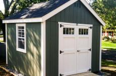 Wooden cape cod storage shed with double door, gable vents, and wooden ramp