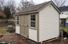 Vinyl cape cod storage shed with double wooden doors, two windows, gable vents