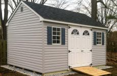 Vinyl cape cod storage shed with double steel slab doors with wooden ramp