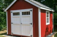 Wooden cape cod storage shed with double doors and two windows