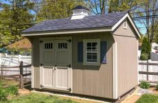Wooden quaker storage shed with cupola, window, and double doors
