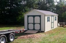 Wooden a-frame storage shed with double end doors, single side door, two windows, and wooden ramp