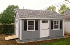 Wooden cape code storage shed with end double doors, two windows, side door, and wooden ramp
