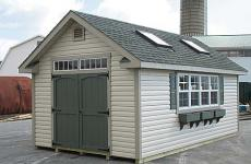 Vinyl cape cod storage shed with wooden double doors, transom windows, skylights, gable vents, and flower boxes