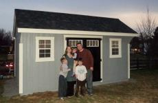 Wooden Quaker stye storage shed with double doors and two windows
