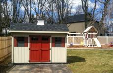 Wooden quaker style storage shed with double doors, two windows, and cupola