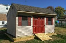 Vinyl quaker shed with double doors, two windows and wooden ramp