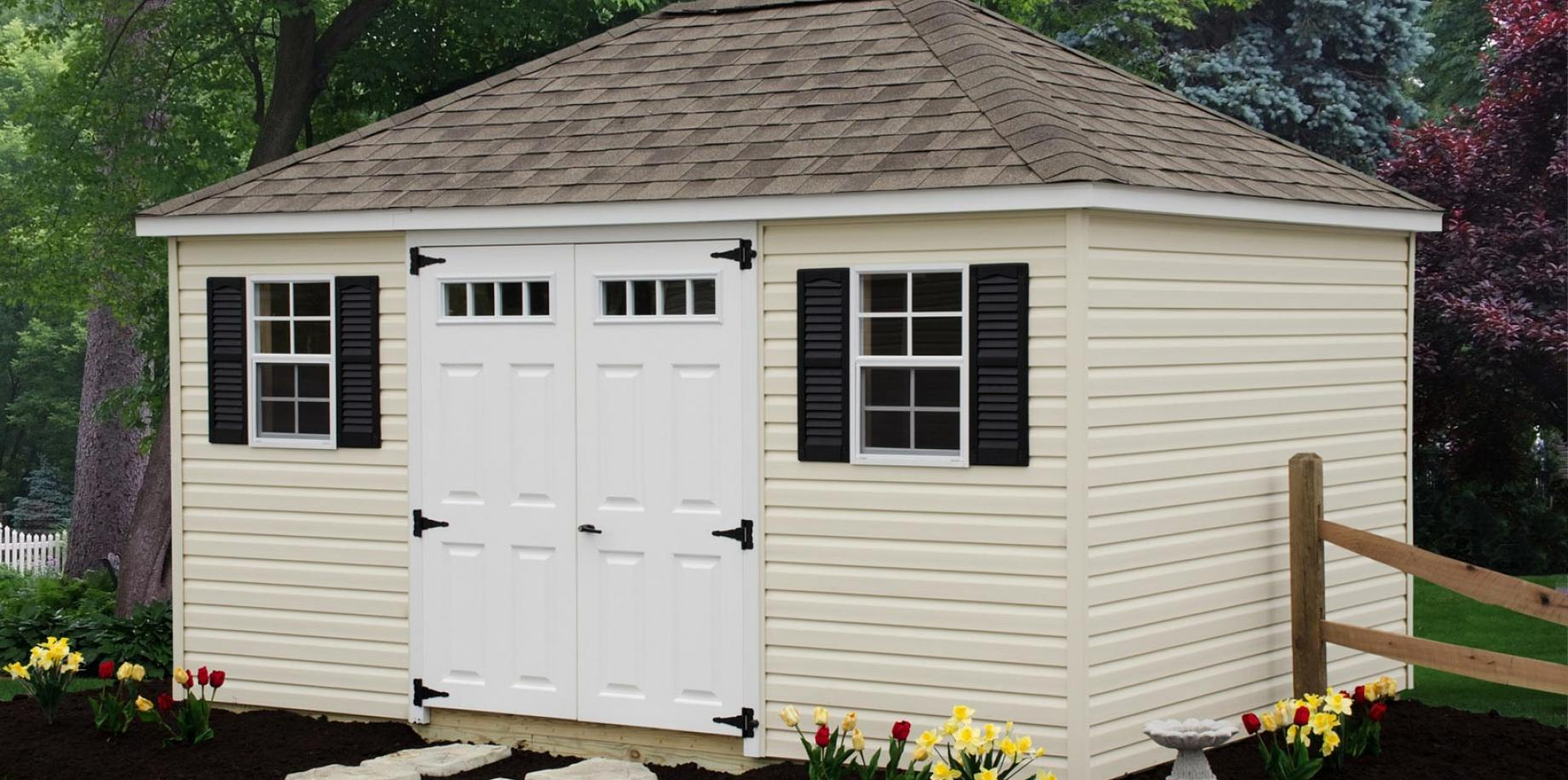 Hip-roof style shed with vinyl siding.