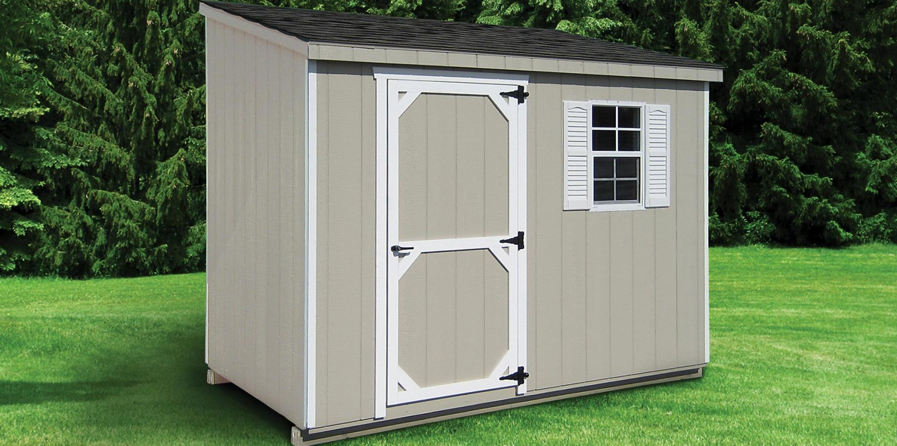 A Lean-To shed with wood siding painted gray